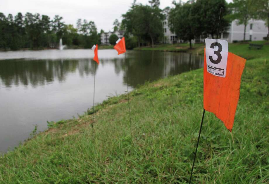 Orange evidence flags line the shore of a pond where police say a man attempted to drown his daughters. Alan Tysheen Lassiter faces three counts of attempted murder: one for each of the girls and a third for their 7-year-old brother, who ran away to seek help, police say. Photo: Allen G. Breed, STF / AP