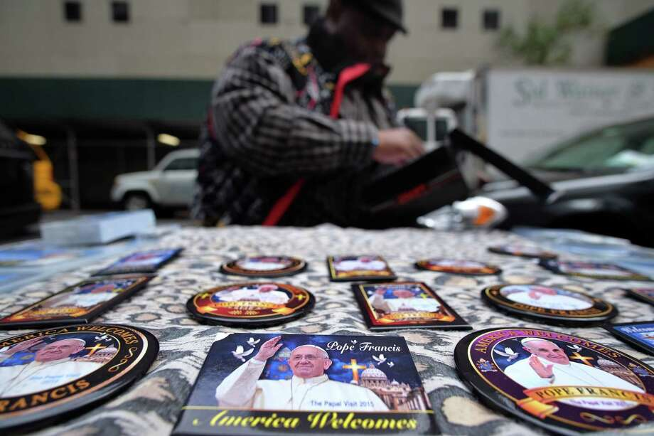 A vendor arranges his roadside stall with Pope Francis memorabilia in New York on September 22, 2015. Pope Francis left Cuba on September 22 for his first-ever visit to the US, where he will meet President Barack Obama and give landmark addresses to Congress and the United Nations. AFP PHOTO/JEWEL SAMADJEWEL SAMAD/AFP/Getty Images Photo: JEWEL SAMAD / AFP