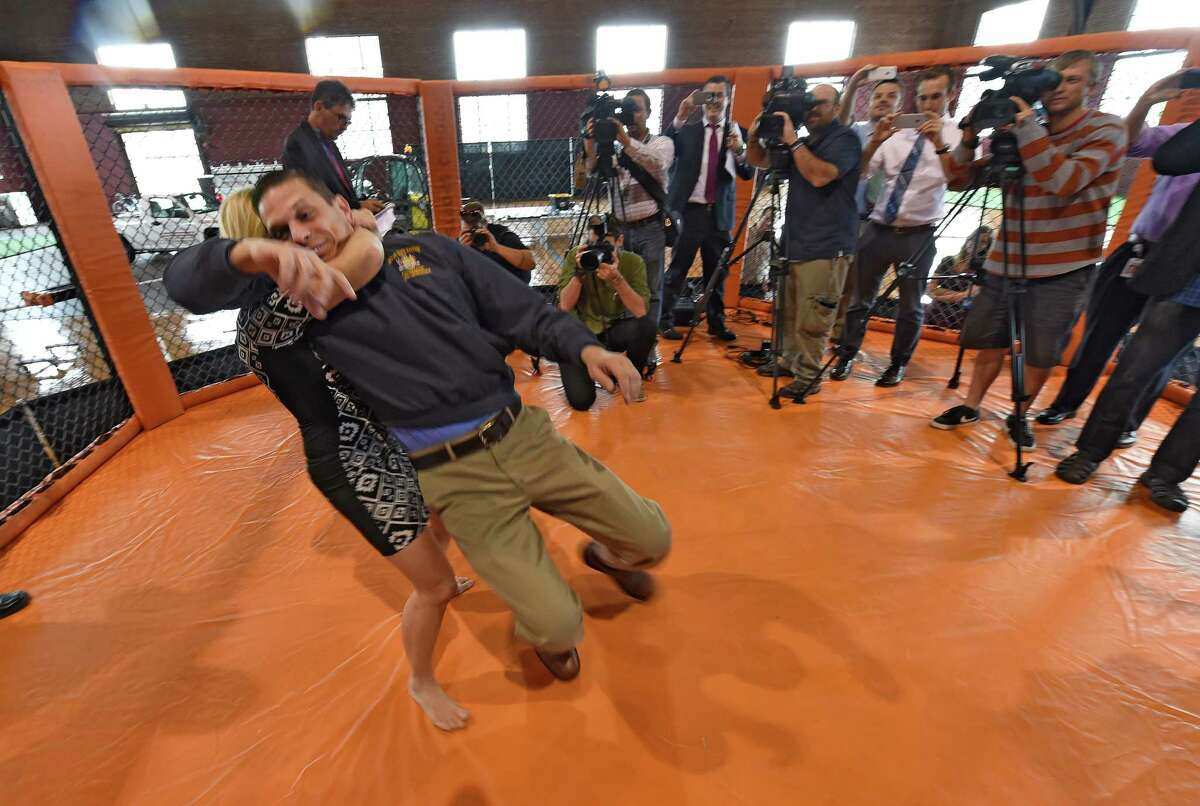 Assemblyman Angelo Santabarbara taken to the mat in the octagon ring by 40 year old mother of two, Malinda Diffee while promoting the upcoming Amateur MMA fight Tuesday Sept. 22, 2015 at the Schenectady Armory in Schenectady, N.Y. The fight card will take place Saturday night at the Armory. (Skip Dickstein/Times Union)