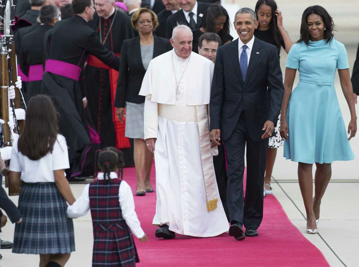 Pope Francis walks alongside US President Barack Obama and First Lady Michelle Obama upon arrival at Andrews Air Force Base in Maryland, September 22, 2015, on the starjt of a 3-day trip to Washington. AFP PHOTO / SAUL LOEBSAUL LOEB/AFP/Getty Images