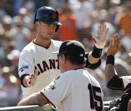 San Francisco Giants' Buster Posey is greeted in the dugout after hitting a three-run homer against the Arizona Diamondbacks during the sixth inning of a baseball game, Sunday, Sept. 20, 2015, in San Francisco. (AP Photo/George Nikitin)