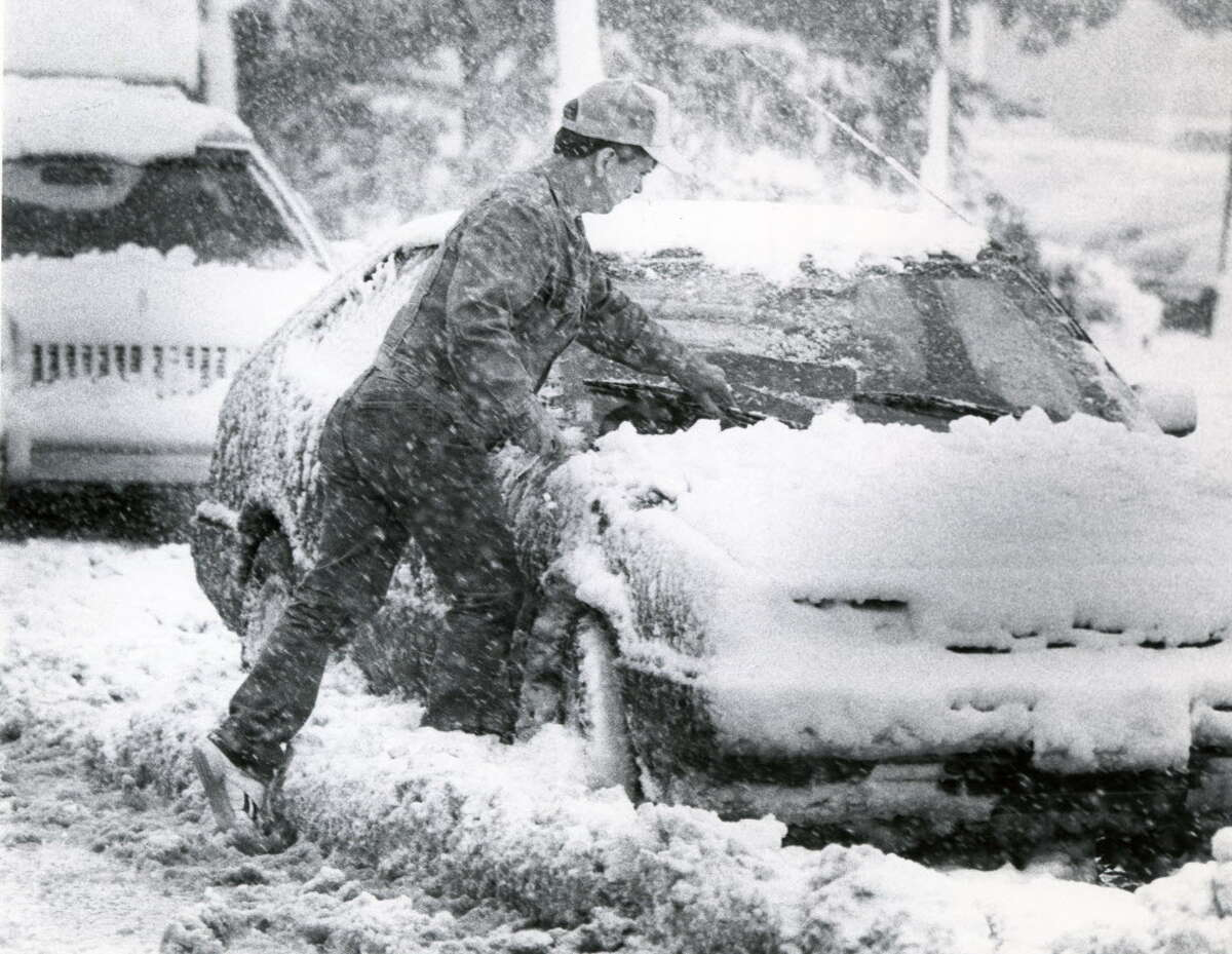 Cleaning snow off car at Albany Co. Airport in Albany, N.Y., Oct. 4, 1987. (John Carl D'Annibale / Times Union archive)