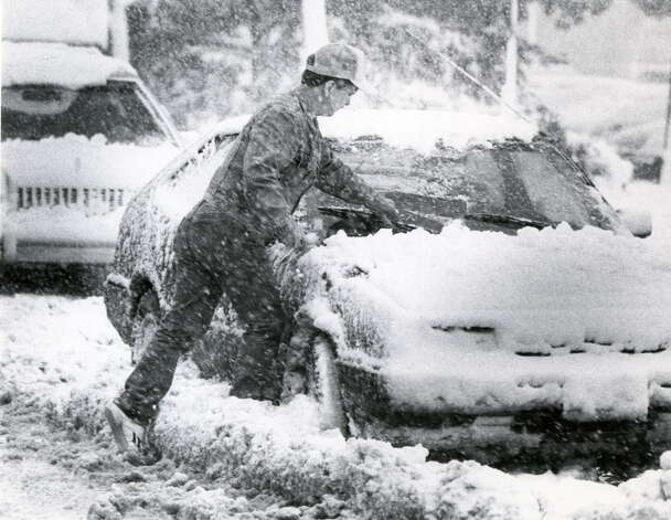 Cleaning snow off car at Albany Co. Airport  in Albany, N.Y., Oct. 4, 1987.  (John Carl D'Annibale / Times Union archive) / ALBANY TIMES UNION