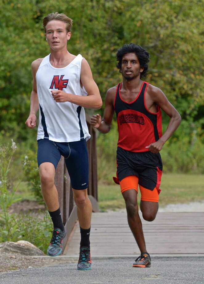 New Fairfield's Michael Rautter, left, won and Pomperaug's Alexander Abraham finished second in the boys high school cross country meet between New Fairfield, Pomperaug, New Milford and Masuk high schools on Tuesday afternoon, September 22, 2015, at Great Hollow Lake at Wolfe park, in Monroe, Conn. Photo: H John Voorhees III / Hearst Connecticut Media / The News-Times