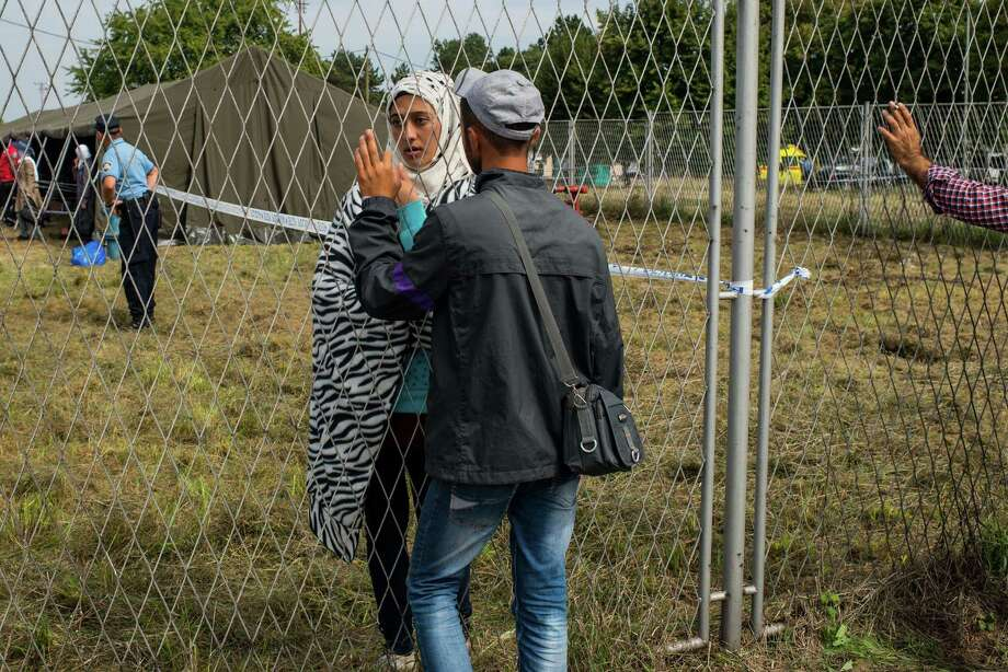 OPATOVAC, CROATIA - SEPTEMBER 22:  Migrants talk through the fence of a refugee camp as more migrants arrive from the Serbian border on September 22, 2015 in Opatovac, Croatia. Croatia has built a refugee camp to control the transit of migrants to Hungary with a capacity of 4,000 people. Thousands of migrants have arrived in Austria over the weekend with more en-route from Hungary, Croatia and Slovenia. Politicians across the European Union are to hold meetings on the refugee crisis with EU interior ministers meeting tomorrow and EU leaders attending an extraordinary summit on Wednesday.  (Photo by David Ramos/Getty Images) Photo: David Ramos, Stringer / Getty Images / 2015 Getty Images