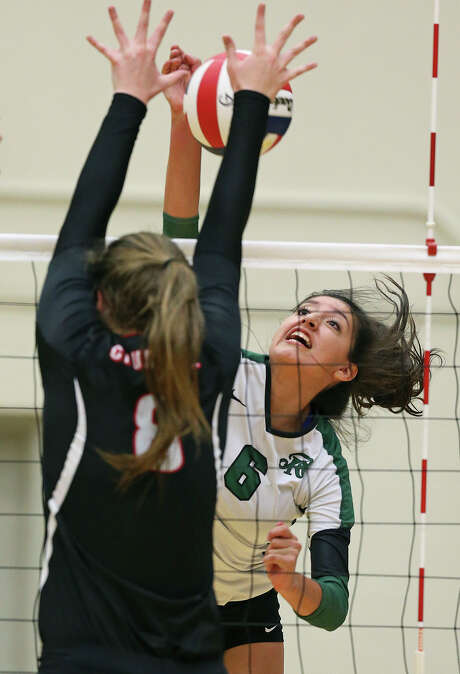 Elisa Barbosa fires a shot into BrynCaitlyn Walker for the Rattlers as Reagan plays Churchill at Littleton Gym on Sept. 22, 2015 in a battle of top rated volleyball teams. Photo: Tom Reel /San Antonio Express-News
