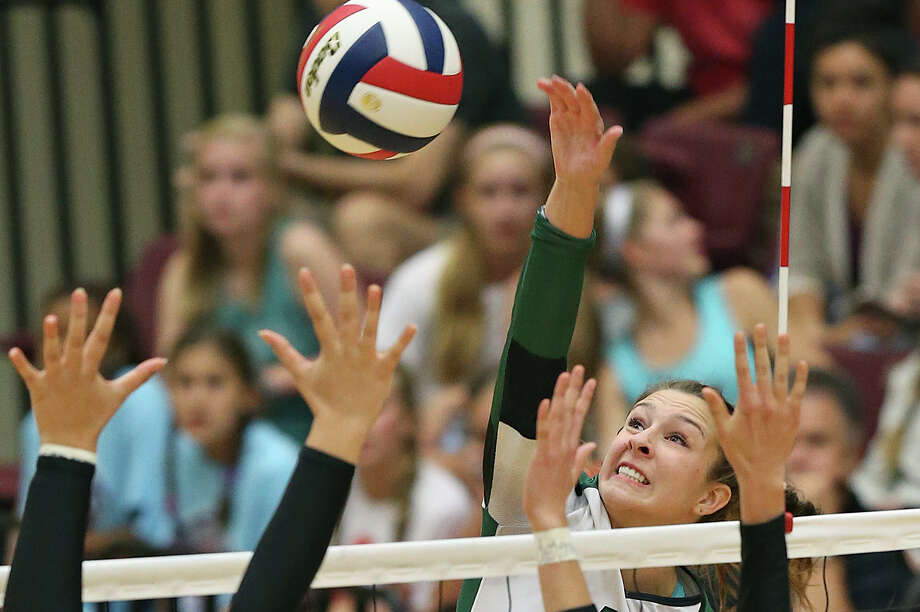 Rattler Camryn Ennis elevates over Morgan Vacek and Ashlyn Teis (15) as Reagan plays Churchill at Littleton Gym on Sept. 22, 2015 in a battle of top-rated volleyball teams. Photo: Tom Reel /San Antonio Express-News