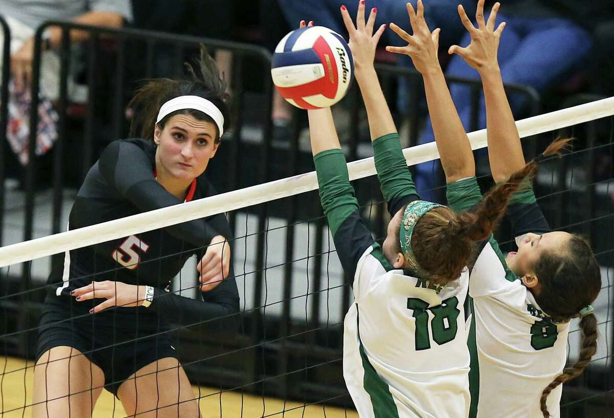 Abby Buckingham of the Chargers blows a ball by Lauren Schilling (18) and Faith Squier as Reagan plays Churchill at Littleton Gym on Sept. 22, 2015 in a battle of top rated volleyball teams.
