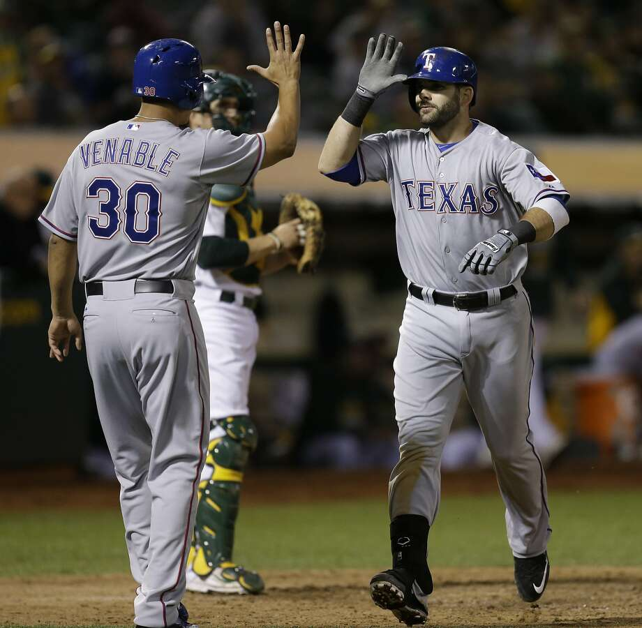 Texas Rangers' Mitch Moreland, right, is congratulated by Will Venable (30) after hitting a two-run home run off Oakland Athletics' Sean Nolin during the sixth inning of a baseball game Tuesday, Sept. 22, 2015, in Oakland, Calif. (AP Photo/Ben Margot) Photo: Ben Margot, Associated Press