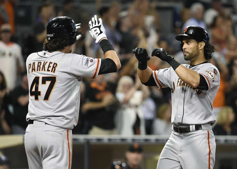 Angel Pagan #16 of the San Francisco Giants, right, is congratulated by Jarrett Parker #47 after hitting a two-run home run during the seventh inning of a baseball game against the San Diego Padres at Petco Park September 22, 2015 in San Diego, California. Photo: Denis Poroy, Getty Images
