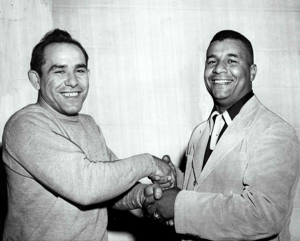 Yogi Berra (L) and Brooklyn Dodgers catcher Roy Campanella congratulate each other at the American Baseball Academy for the first time after each won a Most Valuable Player award. Campanella was voted MVP the National League, and Berra won the corresponding title for the American League circa November 1951 in New York.
