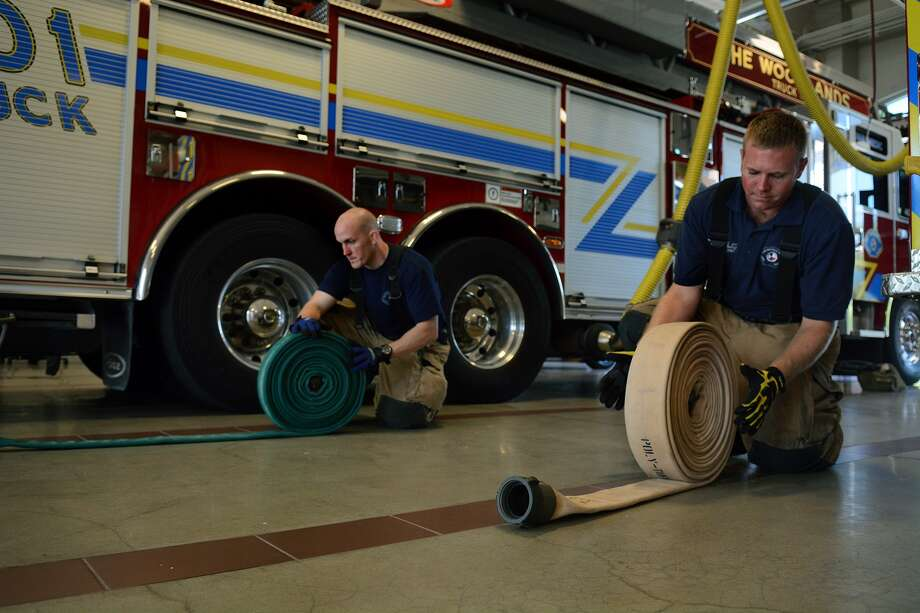 Firefighters Jacob Austin, left, and Justin Jones roll hoses during their 24 hr. shift at The Woodlands Fire Dept. Fire Station 1. (Photo by Jerry Baker/Freelance) Photo: Jerry Baker, Freelance