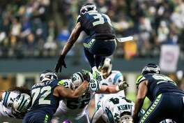Kam Chancellor, top, leaps over his team's defensive line in an attempt to block a Panthers field goal during the first half of a NFC Divisional Playoffs game Saturday, January 10, 2015, at CenturyLink Field in Seattle, Washington.