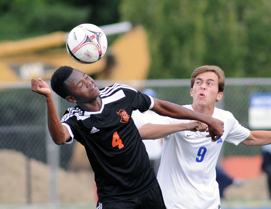 Stamford's Ibra Diallo, left, heads the ball as Darien's Sean Gallagher approaches during Tuesday's boys soccer game. Photo: Bob Luckey Jr. / Hearst Connecticut Media / Greenwich Time