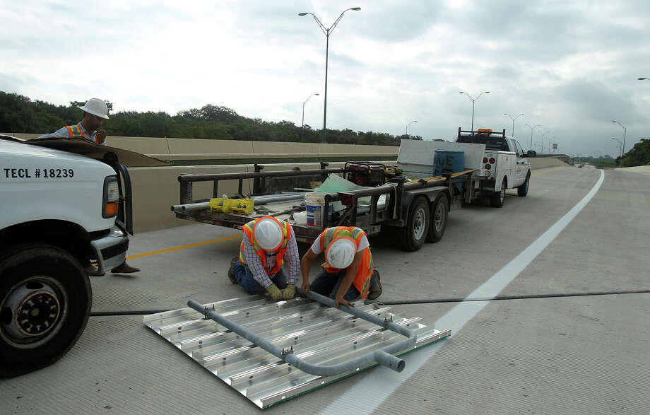 The westbound lanes of Wurzbach Parkway will open between noon and 5 p.m. today. Earlier this month, a construction crew assembled an exit sign in preparaton for the opening of the eastbound half of Wurzbach between West Avenue and Jones Maltsberger Road. Photo: John Davenport /San Antonio Express-News / ©San Antonio Express-News/John Davenport