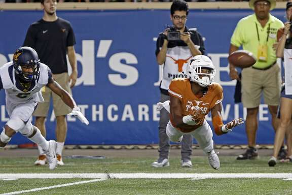 Texas receiver John Burt (1) catches a pass against California defensive back Darius White during the first half of an NCAA college football game, Saturday, Sept. 19, 2015, in Austin, Texas. (AP Photo/Michael Thomas)