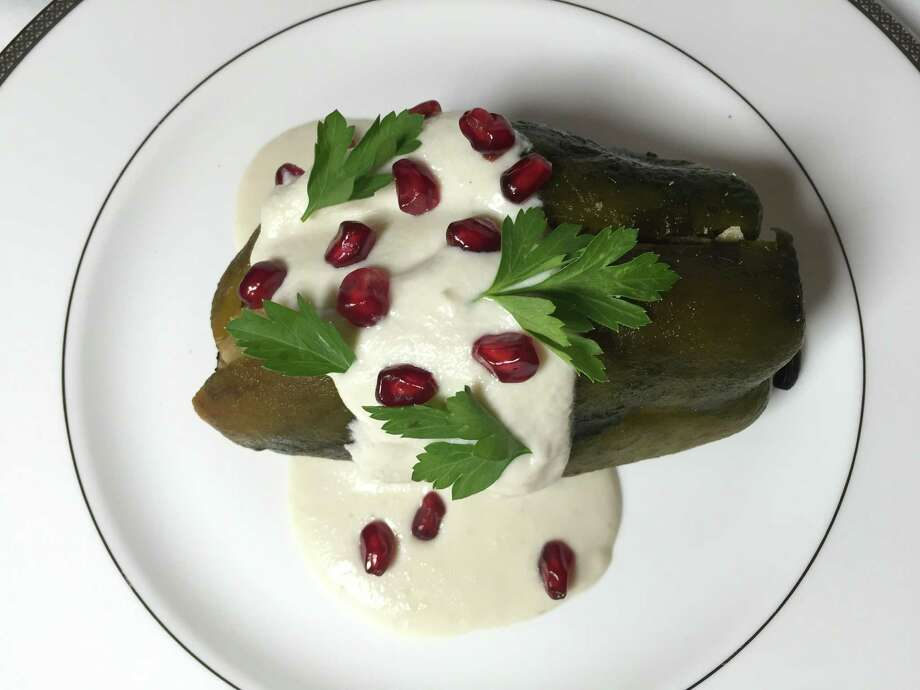 Chiles en nogada consists of a poblano chile stuffed with a sweet and savory meat mixture and topped with a walnut sauce, pomegranate seeds and parsley leaves Photo: Edmund Tijerina /San Antonio Express-News