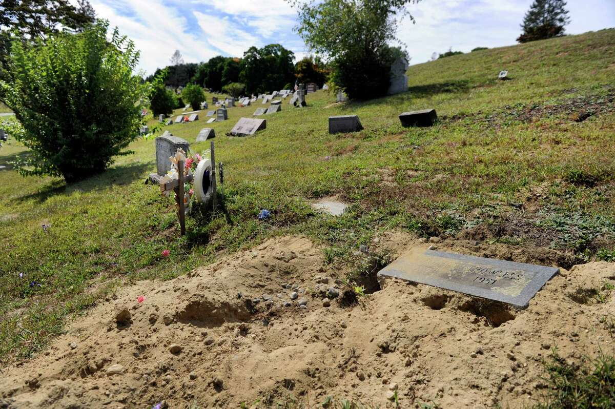 Mike Sennello, superintendent of Center Cemetery in New Milford, says this grave stone pictured, which has been repaired several times, is probably the most serious example of damage created by an overpopulation of woodchucks at the cemetery, Monday, Sept. 21, 2015.