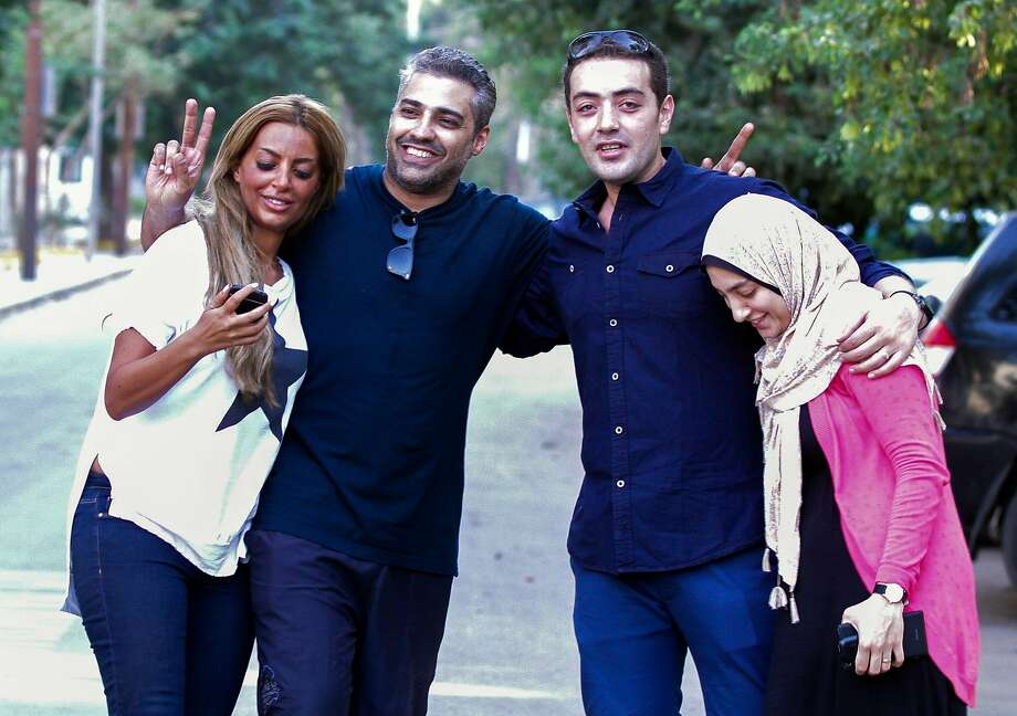 Mohamed Fahmy (second from left) and his wife, Marwa Omara (left), and Baher Mohammed and his wife, Jihan, celebrate in Cairo after the men were released from prison. Photo: Str, AFP / Getty Images