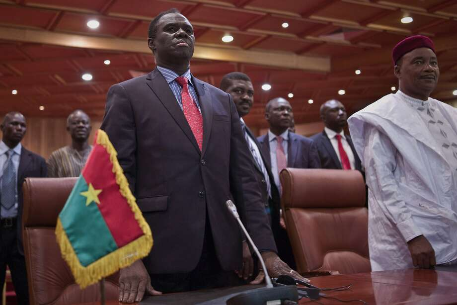 Burkina Faso's transitional President Michel Kafando (left) stands next to Niger's President, Mahamadou Issoufou during a official handover ceremony in Ouagadougou, Burkina Faso, Wednesday. Amid cheers and the national anthem, Burkina Faso's interim president took charge of the country again Wednesday a week after a military general and his supporters overthrew him and his transitional government. Interim President Michel Kafando and Prime Minister Yacouba Isaac Zida marked their return to power in an official handover ceremony in Ouagadougou. Photo: Str, Associated Press