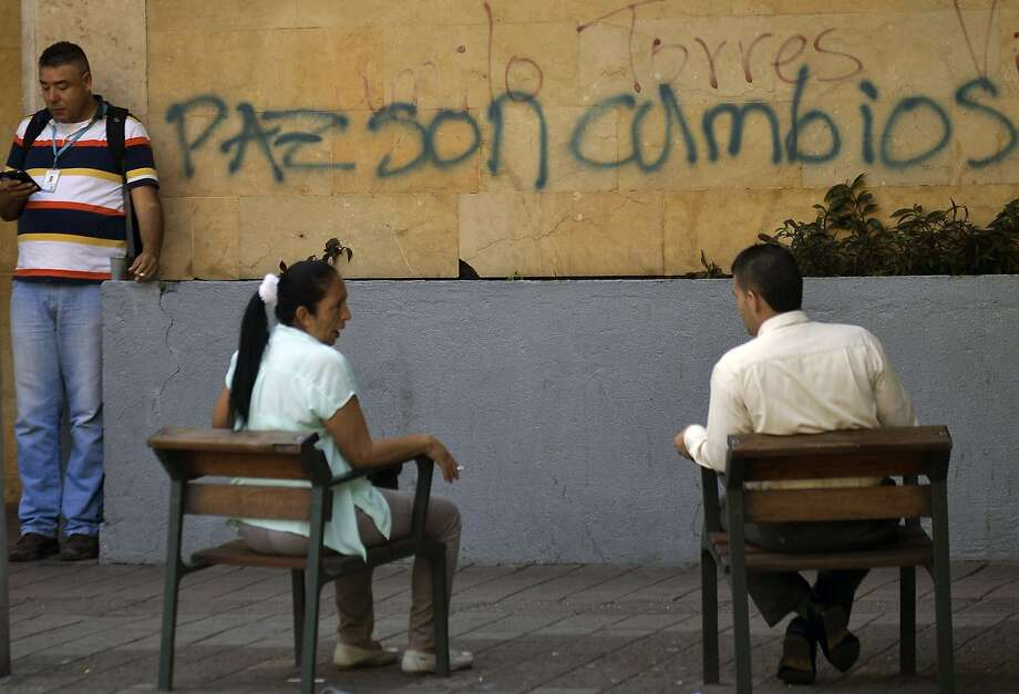 "People relax next to graffiti of the FARC guerrillas reading ""Peace are Changes"" at Antioquia university in Medellin, Antioquia department, Colombia. Colombia's FARC rebels said Wednesday that ""peace has arrived"" as their leader flew in to meet for the first time with President Juan Manuel Santos at peace talks in Cuba. ""Timoleon Jimenez has arrived in Havana,"" the rebels' negotiating team at the talks, which aim to end the half-century conflict, wrote on its Twitter account. It posted a picture of the FARC leader with the caption ""peace has arrived."" Photo: Raul Arboleda, AFP / Getty Images"