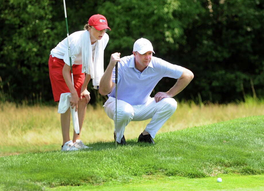 David Hayes of Loudenville, right, eyes up a putt with his son, Patrick, 14, in the final round of the Capital Stroke Play on Saturday, Aug. 4, 2012, at the Schuyler Meadows Club in Loudenville, N.Y. The Capital Stroke Play is the signature event of the Capital Region Amateur Golf Association Tour. (Cindy Schultz / Times Union) Photo: Cindy Schultz / 00017424A