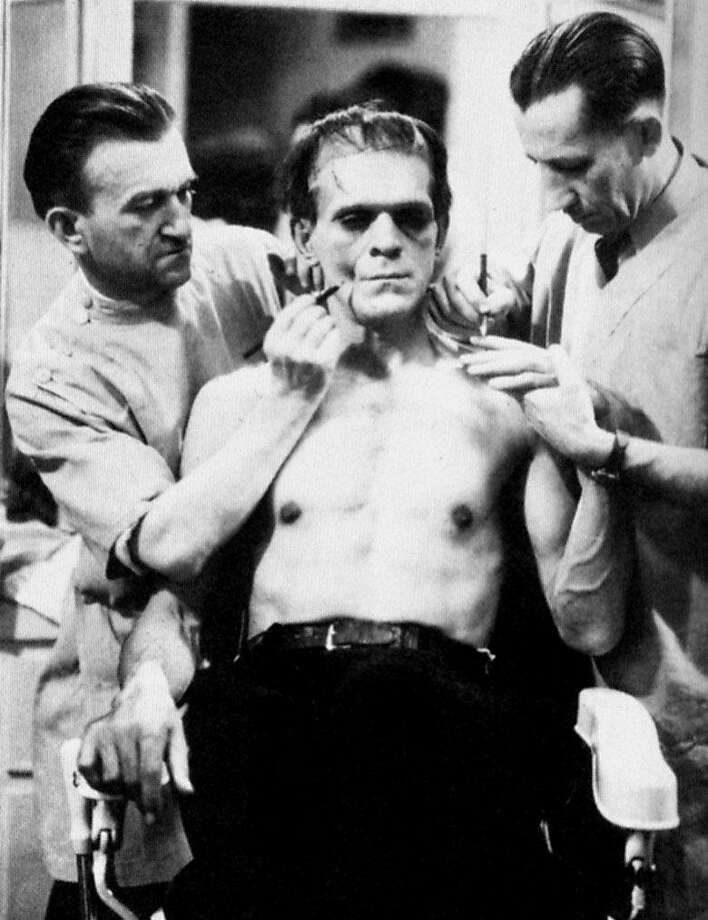 """Jack Pierce (left) preps Boris Karloff for his role as the title character in 1931's """"Frankenstein. El Cerrito filmmaker Strephon Taylor's """"Jack Pierce: The Man Who Made Monsters"""" Hi, for karloff28 in Pink 5/28, need the following picture of Boris Karloff, center, being made up as Frankenstein's monster by makeup man Jack Pierce, left (guy at right is not identified).Ê Please slug it Karloff28_frankenstein. Ran on: 05-28-2006 The Balboa series will include footage of Boris Karloff, center, being made up as Franken- stein's monster by Jack Pierce, left. Photo: Ho"""