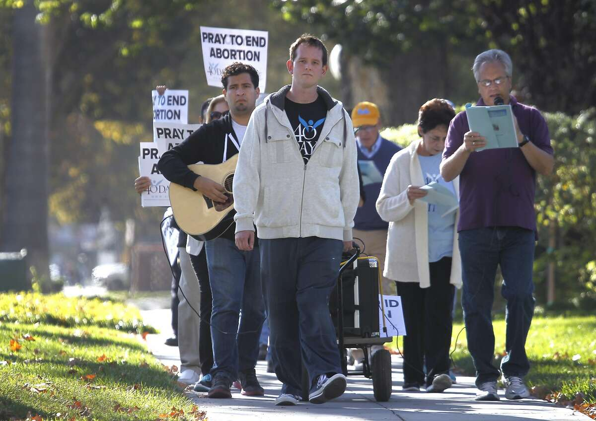 Anti-abortion activists march on The Alameda in San Jose, Calif. to a Planned Parenthood office where the group held a vigil on Wednesday, Sept. 23, 2015. The action is part of the nationwide 40 Days For Life movement.