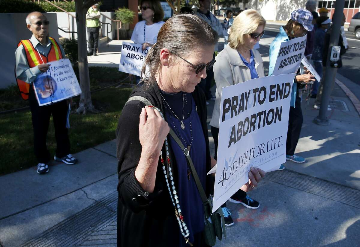 Katherine Cottingham prays with other anti-abortion protesters during a vigil in front of a Planned Parenthood office in San Jose, Calif. on Wednesday, Sept. 23, 2015. The action is part of the nationwide 40 Days For Life movement.