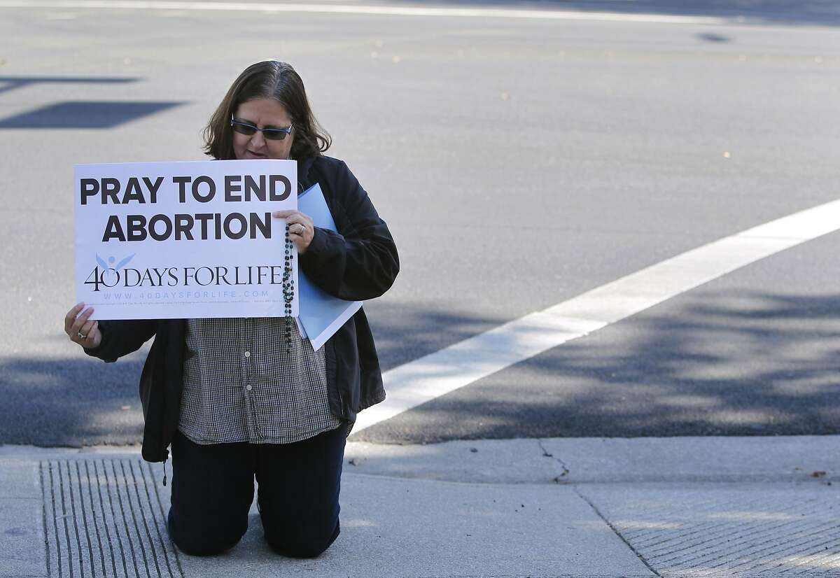 Anne Marie Chrisoulis kneels in prayer outside of a Planned Parenthood office in San Jose, Calif. on Wednesday, Sept. 23, 2015. The action is part of the nationwide 40 Days For Life movement.