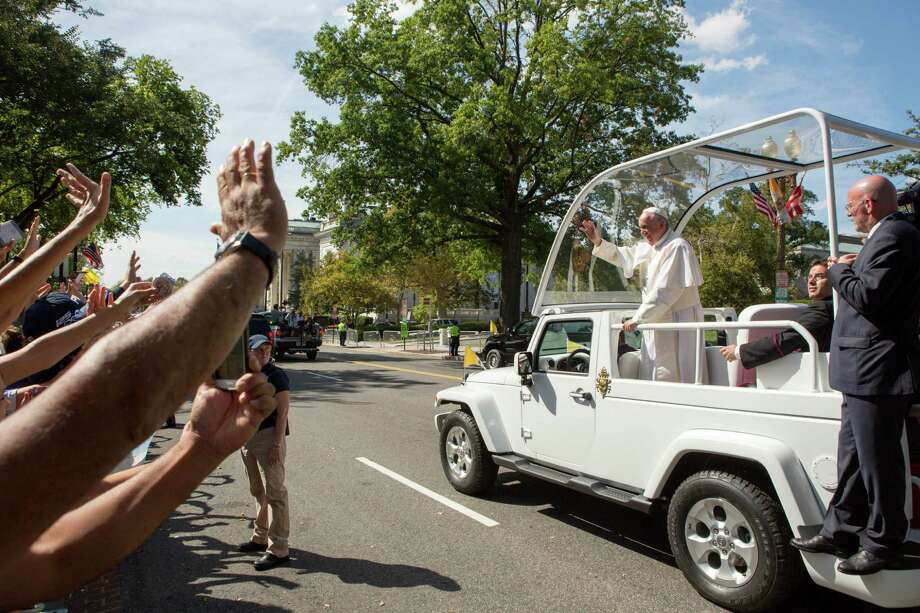 Pope Francis waves to the crowd as he rides in a popemobile along a parade route around the National Mall on Wednesday. Photo: Allison Shelley / Getty Images / 2015 Getty Images