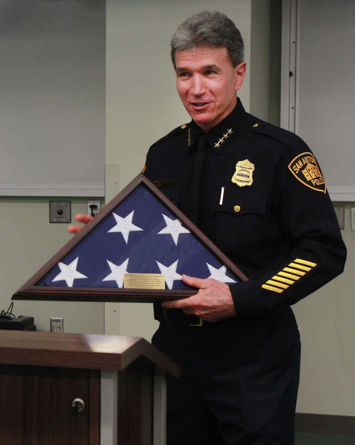 San Antonio Police Chief William McManus holds a keepsake flag that was given to him Thursday December 18, 2014 at a goodbye breakfast held in McManus' honor at the Public Safety Headquarters. McManus is leaving the police department to take a position with City Public Service.