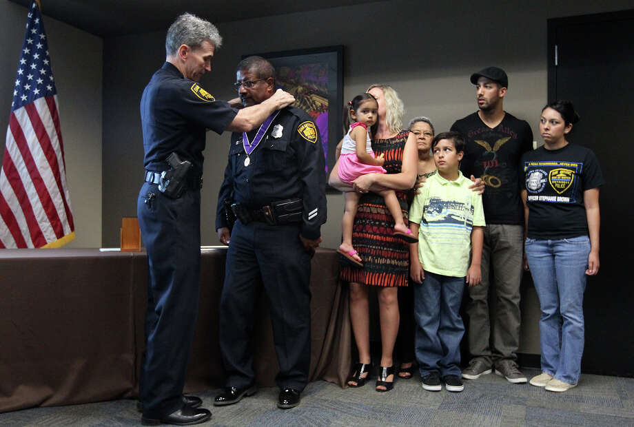San Antonio Police Chief William McManus (left) places the department's Purple Heart medal around police officer Stanley Brown who accepted in honor of his daughter and slain police officer Stephanie Brown while his family looks on during a ceremony at the Alamodome on Saturday, Sept. 8, 2012. Stephanie Brown was killed last March while on duty when her police vehicle was struck by a suspected drunk driver. Stephanie Brown's daughter, Audrey, was also in attendance for the ceremony. Photo: Kin Man Hui, Staff / SAN ANTONIO EXPRESS-NEWS / ©2012 San Antonio Express-News