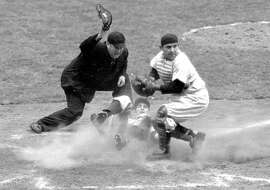 "FILE - In this Oct. 6, 1950, file photo, Philadelphia Phillies shortstop Granny Hamner is tagged at the plate by New York Yankees catcher Yogi Berra as he tries to score from third in the ninth inning of Game 3 of baseball's World Series at Yankee Stadium in New York.  The Hall of Fame catcher renowned as much for his lovable, linguistically dizzying ""Yogi-isms"" as his unmatched 10 World Series championships with the New York Yankees, died Tuesday, Sept. 22, 2015. He was 90.  (AP Photo/File)"