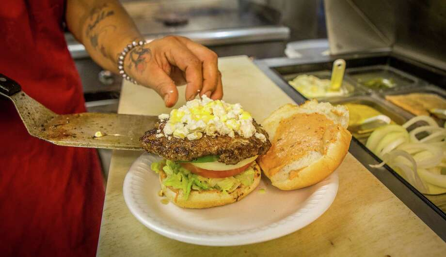 A kitchen worker assembles a burger at The Hubcap Grill's 19th Street location. Photo: Nick De La Torre, For The Chronicle / ONLINE_YES