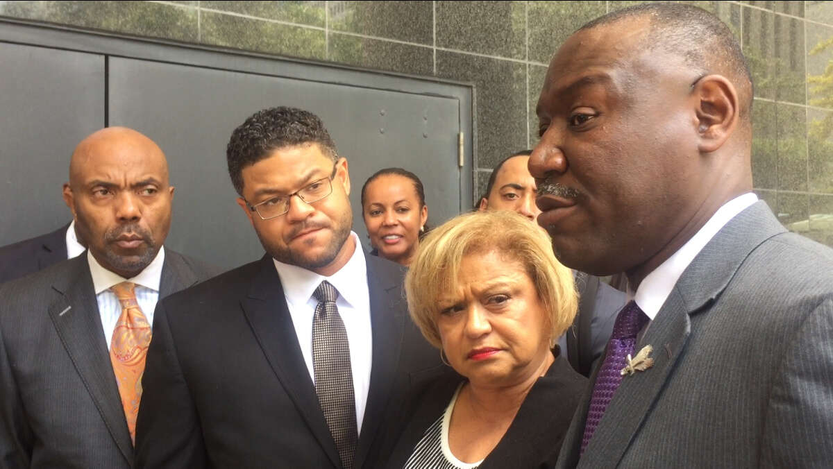 Robbie Tolan, left, with glasses, outside the Houston federal courthouse with lawyer Benjamin Crump, right, Tuesday, Sept. 15, 2015 in Houston, Texas, after a settlement had been reached between Tolan and his relatives with Bellaire, Texas and officer Jeffrey Cotton to be paid by the City of Bellaire. (Cindy George / Houston Chronicle)