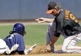San Francisco Giants second baseman Kevin Frandsen picks off Milwaukee Brewers' Rickie Weeks at second base during the first inning of a spring training baseball game Saturday, March 6, 2010, in Phoenix.