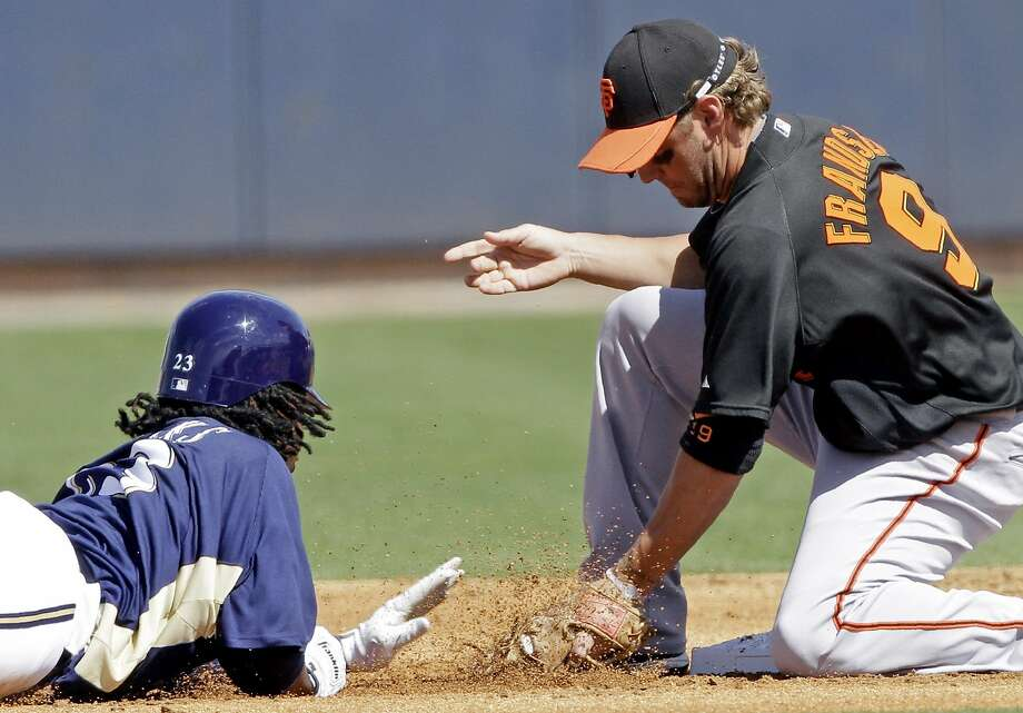San Francisco Giants second baseman Kevin Frandsen picks off Milwaukee Brewers' Rickie Weeks at second base during the first inning of a spring training baseball game Saturday, March 6, 2010, in Phoenix. Photo: Morry Gash, AP