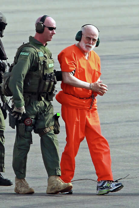 "FILE - In this Thursday, June 30, 2011 file photo, James ""Whitey"" Bulger, right, is escorted from a U.S. Coast Guard helicopter to a waiting vehicle at an airport in Plymouth, Mass., after attending hearings in federal court in Boston. Bulger was convicted of numerous crimes in 2013 after 16 years on the run. Phil Castinetti, of Peabody, Mass., said he has the orange top Bulger wore and has received a $25,000 bid for it. People are peddling all types of Bulger memorabilia as the ""Black Mass,"" a movie about the notorious gangster, hits theaters in September 2015. Some of Bulger's victims are not amused.  (AP Photo/Boston Herald, Stuart Cahill, File)  MANDATORY CREDIT: BOSTON HERALD PHOTO BY STUART CAHILL. NO INTERNET USE. NO TV USE.  NO SALES. BOSTON OUT, MAGS OUT Photo: Stuart Cahill, MBR / Boston Herald"