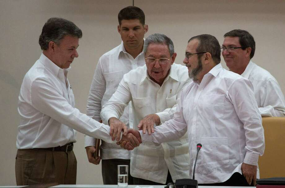 Cuba's President Raul Castro, center, encourages Colombian President Juan Manuel Santos, left, and Commander the Revolutionary Armed Forces of Colombia or FARC, Timoleon Jimenez to shake hands, in Havana, Cuba, Wednesday, Sept. 23, 2015. In a joint statement, Santos and the FARC said they have overcome the last significant obstacle to a peace deal by settling on a formula to compensate victims and punish belligerents for human rights abuses. (AP Photo/Desmond Boylan) Photo: Desmond Boylan, STR / AP
