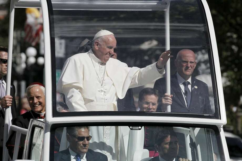 Pope Francis waves to the crowd from the popemobile during a parade in Washington, Wednesday, Sept. 23, 2015. (Alex Brandon/Associated Press)