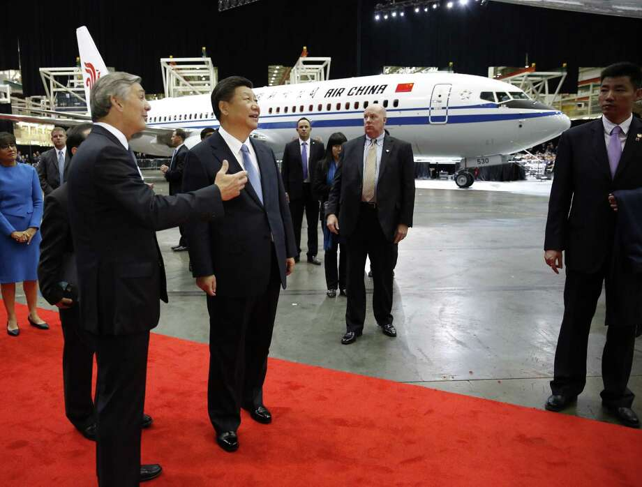 Ray Conner, president of Boeing Commercial Airplanes (left) and Chinese President Xi Jinping tour Boeing's assembly line Wednesday in Everett, Washington. Boeing has made deals with Chinese firms to sell 300 aircrafts. Photo: JASON REDMOND, Pool / AFP