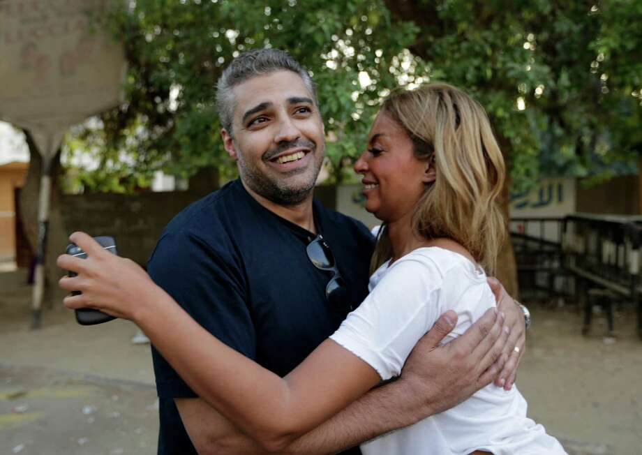 Canadian Al Jazeera English journalist Mohamed Fahmy hugs his wife Marwa Omara after being released from Torah prison in Cairo, Egypt, Wednesday, Sept. 23, 2015. Fahmy and his colleague Baher Mohammed were among a group of 100 people pardoned by Egyptian President Abdel-Fattah el-Sissi on the eve of the major Muslim holiday of Eid al-Adha. The pardon also comes a day before the Egyptian leader is to travel to New York to attend the United Nations General Assembly. (AP Photo/Amr Nabil) ORG XMIT: AMR109 Photo: Amr Nabil / AP