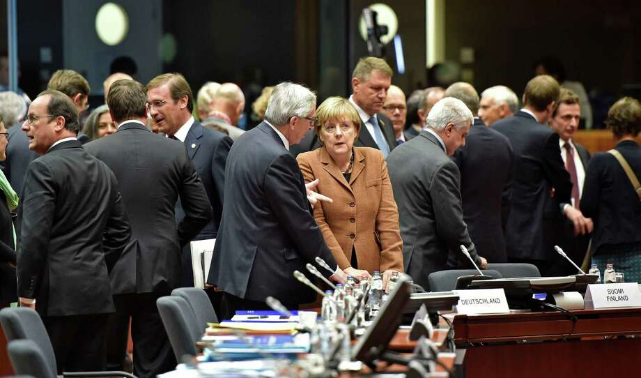 German Chancellor Angela Merkel, center right, listens to European Commission President Jean-Claude Juncker  , center left, as they arrive for an emergency EU heads of state summit on the migrant crisis at the EU Commission headquarters in Brussels on Wednesday, Sept. 23, 2015.  (AP Photo/Martin Meissner) ORG XMIT: MME119 Photo: Martin Meissner / AP