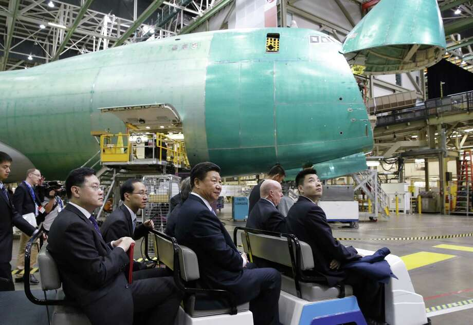 Chinese President Xi Jinping, center, tours the Boeing assembly line, Wednesday, Sept. 23, 2015, in Everett, Wash. Boeing has agreed to buy about 300 jets from Boeing. In addition, state-owned Commercial Aircraft Corp. of China signed a cooperation agreement with the aerospace giant to build a 737 aircraft assembly center in China. (Jason Redmond/Pool Photo via AP) ORG XMIT: NYMV116 Photo: Jason Redmond / Pool Reuters