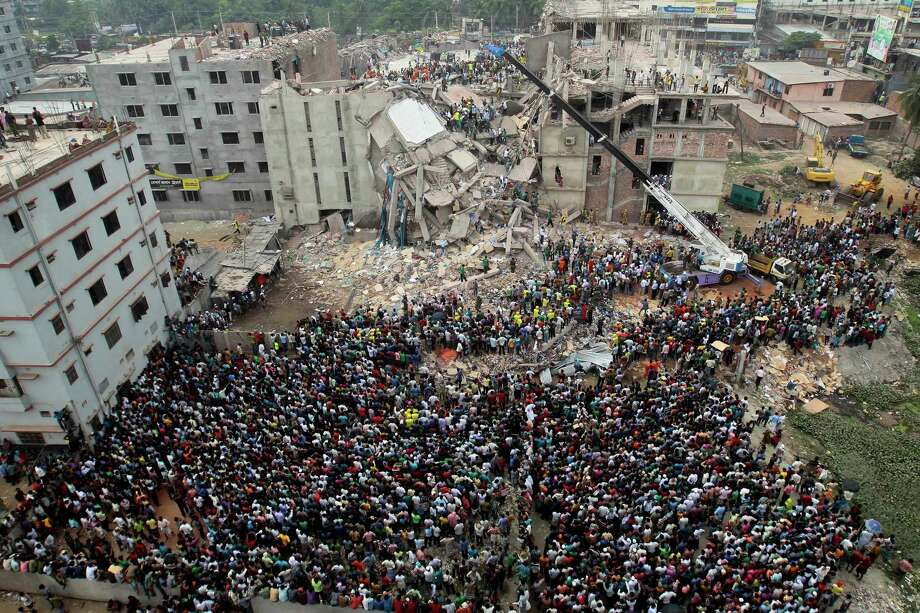 FILE - In this April 25, 2013 file photo, Bangladeshi people gather as rescuers look for survivors and victims at the site of Rana Plaza building that collapsed a day before, in Savar, near Dhaka, Bangladesh. A delegation of the U.S. Trade Representative's office is on a five-day visit to Bangladesh ending Wednesday, Sept. 23, 2015, to see the improvement of safety standards at factory sites and changes to legal documents allowing for wider workers' rights, key conditions for regaining the Generalized System of Preferences facility under which the United States allows imports of more than 5,000 goods from 122 of the world's poorest countries with low or zero-tariff benefits. The trade benefit was withdrawn after the collapse of Rana Plaza, a building complex housing five garment factories outside the capital, Dhaka in 2013. The garment industry is crucial to Bangladesh's economy as it employs about 4 million workers, mostly rural women, and many other sectors including banks are heavily dependent on it. (AP Photo/A.M.Ahad, File) Photo: A.M. Ahad, STR / AP