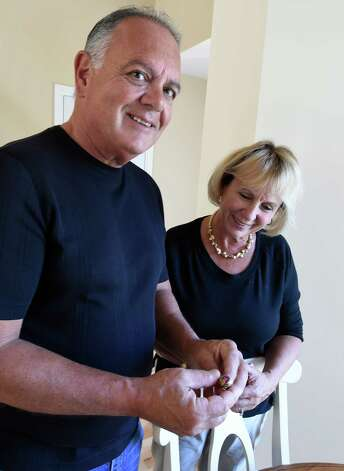 Michael Panucci stands with wife Pat while holding his 1968 Cardinal McCloskey High School class ring that was returned to him Wednesday afternoon, Sept. 23, 2015, at the Panucci's home in Halfmoon, N.Y. An anonymous person found the ring and sent it to the Times Union in the hope that we could locate its rightful owner and return it to them. (Skip Dickstein/Times Union) Photo: SKIP DICKSTEIN / 10033479A