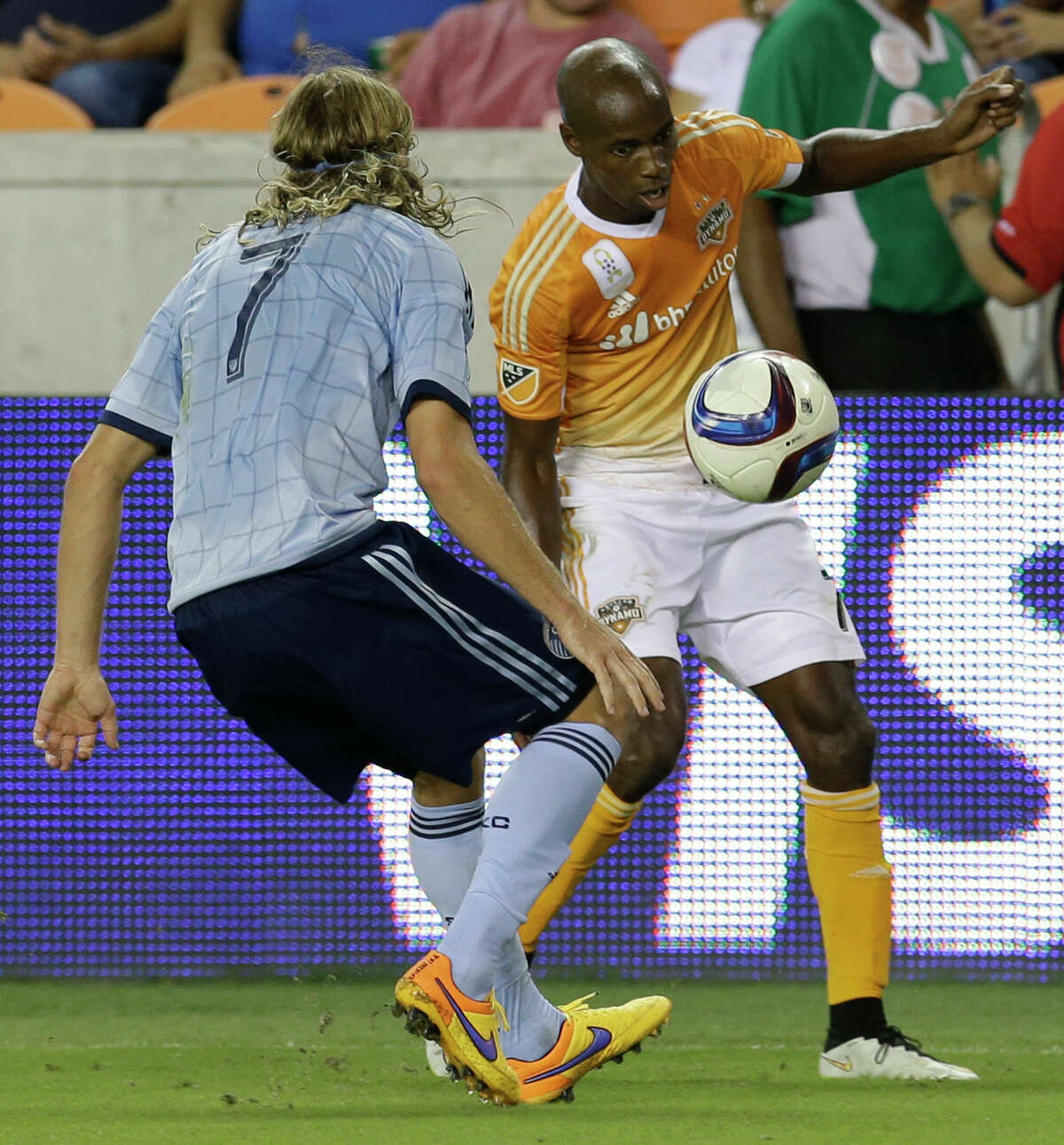 Sporting Kansas City's Chance Myers, left, battles Houston Dynamo's DaMarcus Beasley, right, for the ball during the fist half of MLS game at BBVA Compass Stadium Wednesday, Sept. 23, 2015, in Houston.