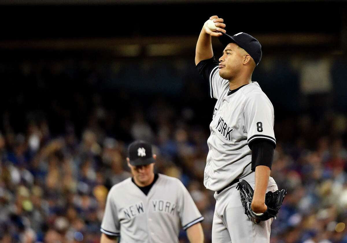New York Yankees starting pitcher Ivan Nova, right, gets ready to be pulled from the baseball game against the Toronto Blue Jays during the sixth inning Wednesday, Sept. 23, 2015, in Toronto. (Nathan Denette/The Canadian Press via AP) ORG XMIT: NSD129