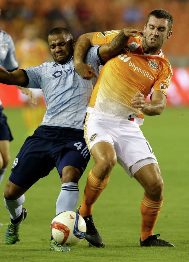 Sporting Kansas City's Kevin Ellis, left, and Houston Dynamo's Will Bruin, right, tangle over the ball during the fist half of MLS game at BBVA Compass Stadium Wednesday, Sept. 23, 2015, in Houston. ( Melissa Phillip  /  Houston Chronicle ) Photo: Melissa Phillip, Staff / © 2015 Houston Chronicle